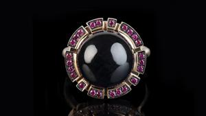 Regina ring with cabochon Australian black sapphire and rubies in 18ct pink gold.